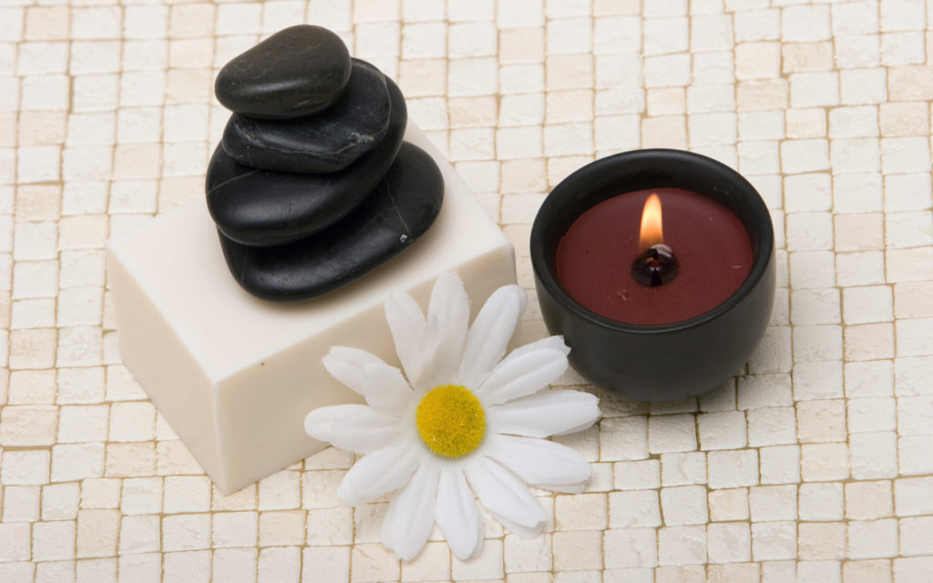Spa stones, soap, lit candle and daisy